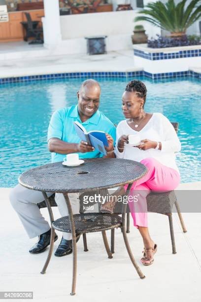Senior African-American couple on pool deck, reading