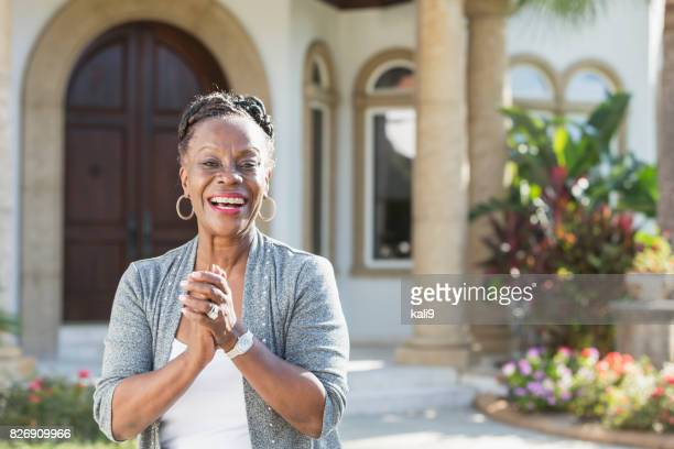 Senior African-American woman standing in front of house