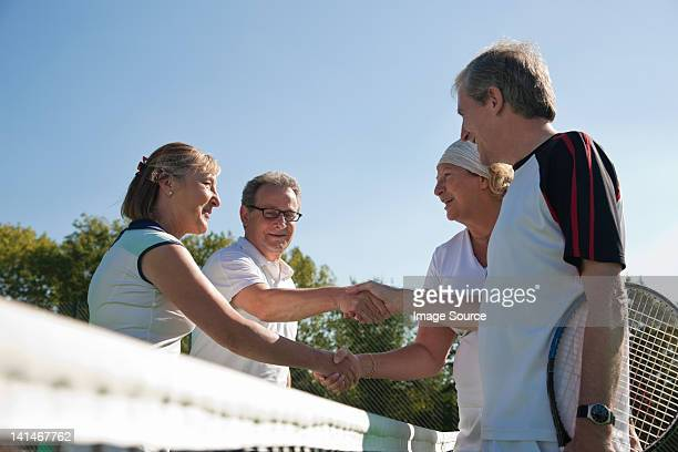 Senior and mature adults shaking hands on tennis court