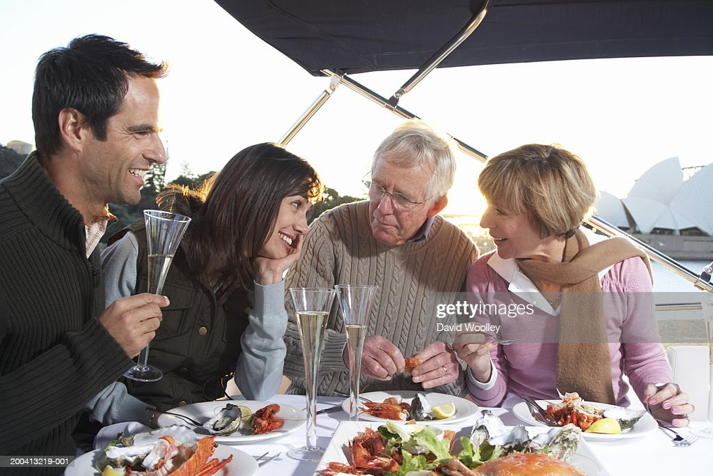 Senior and mature couples having champagne and seafood lunch on yacht : Stock Photo