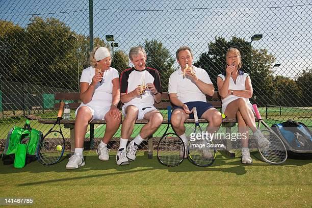 Senior et adulte manger un en-cas sur le court de tennis