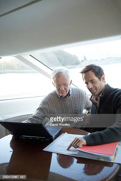 Senior and mature man on yacht using laptop while looking at file