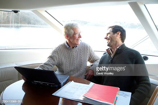 Senior and mature man sitting at table on yacht, smiling at each other