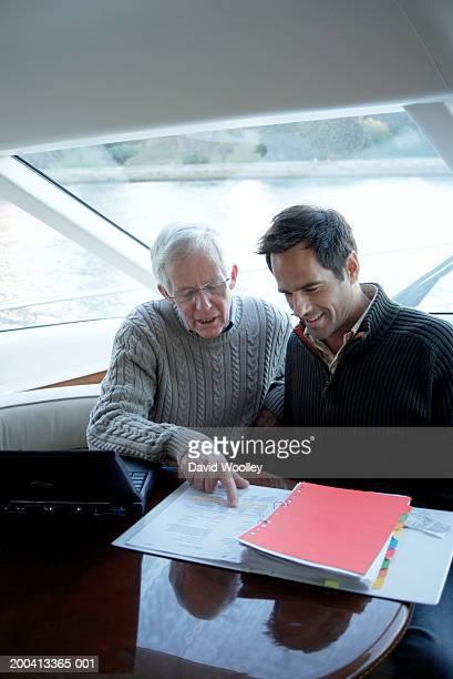 Senior et Homme mûr assis sur un yacht à la recherche