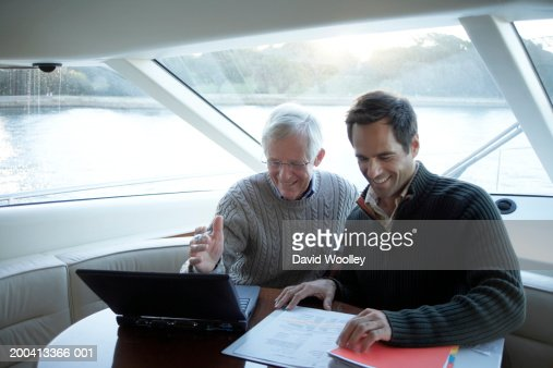 Senior and mature man sitting on yacht using laptop, smiling : Stock Photo