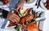 Senior and mature man taking prawns from dish of shellfish, close-up