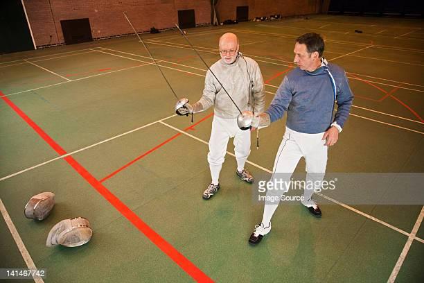 Senior and mature men fencing together