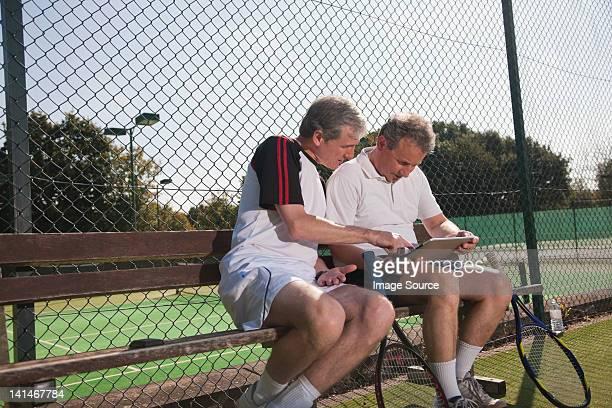 Senior et adulte homme à l'aide de tablette numérique sur le court de tennis