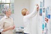Senior and mid adult female fashion designers pinning up ideas