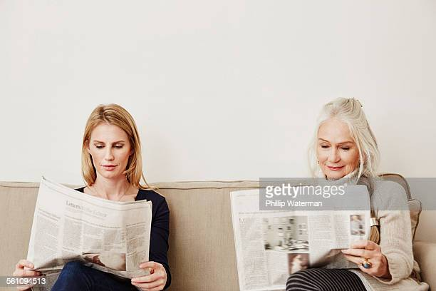 Senior and mid adult women reading newspapers
