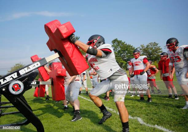 Senior Anthony Griffin hits the sled during a drill at Scarborough High School football practice