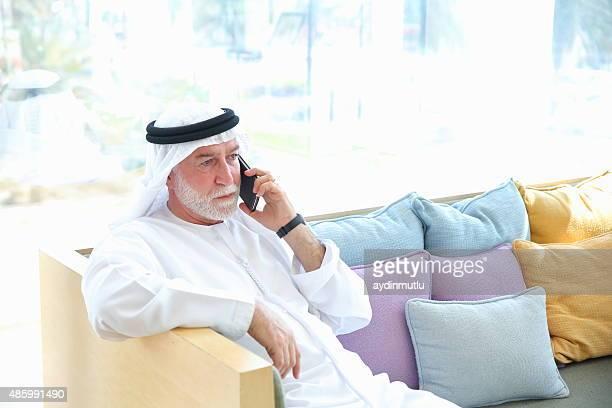 Senior Arabian man talking on phone