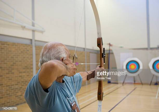 A senior Archer aiming at the target.