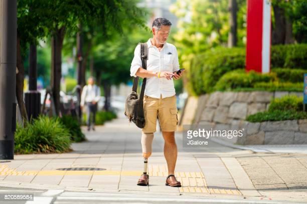道路を横断する待っている間彼の携帯電話をチェック上級アジア切断