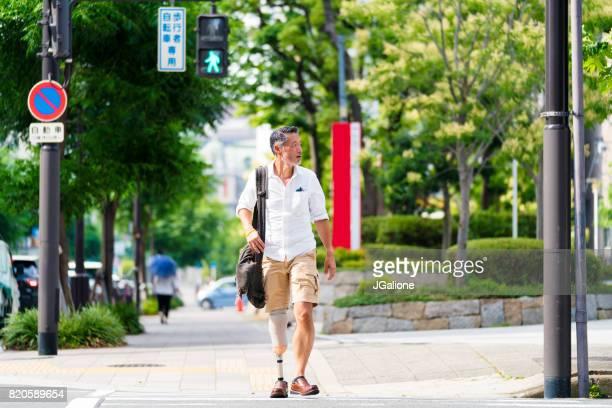 シニアのアジア装着者が道路を横断