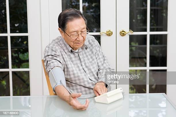Senior Asian Chinese Man Using Blood Pressure Gauge at Home