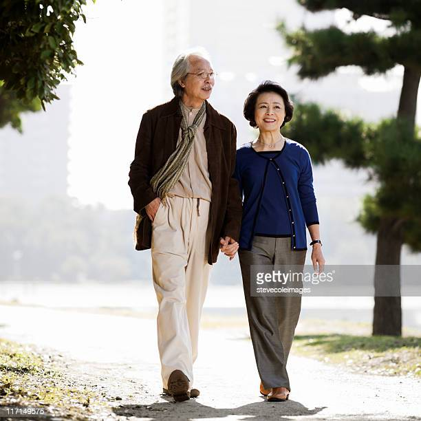 Senior Asian Couple Holding Hands in Park