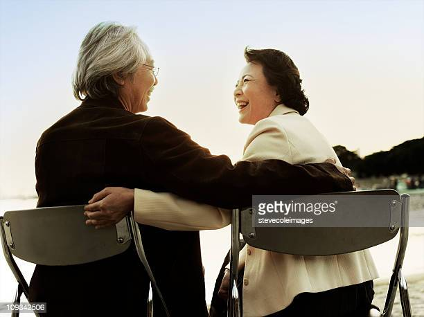 Senior Couple asiatique assise sur la plage