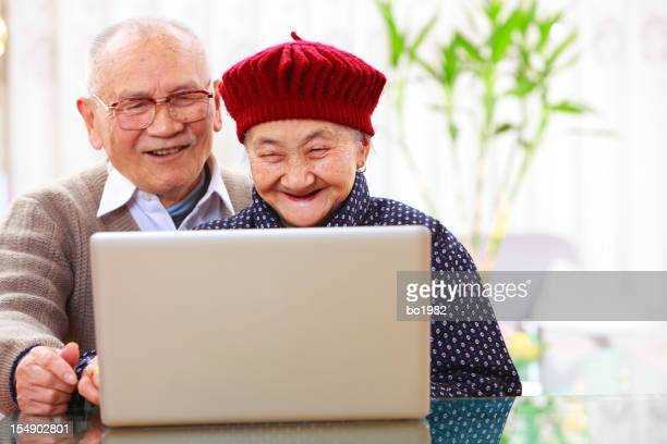 senior asian couple use laptop