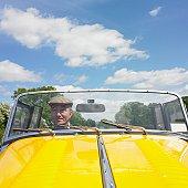 Senior Asian man driving old fashioned sports car
