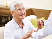 happy and smiling senior asian man in his 80s getting helped by medical worker