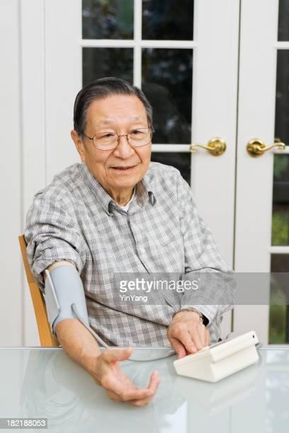 Senior uomo asiatico il monitoraggio della pressione arteriosa