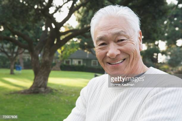 Senior Asian man smiling outdoors