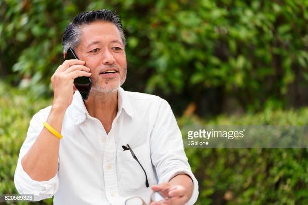 電話で話すアジアの年配の男性