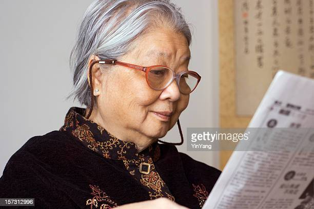 Senior Asian Woman, a Retired, Aging Chinese Grandmother Reading Newspaper