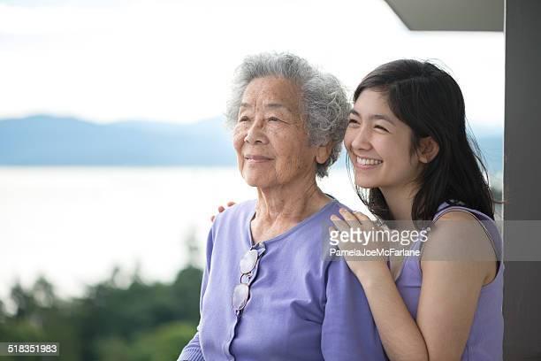 Ältere asiatische Frau mit Enkelin Genießen Sie den Blick vom Balkon