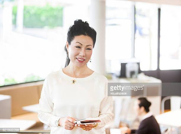 アジアの老人女性明るいカフェで、