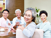 senior asian woman looking at camera smiling while playing cards with friends.