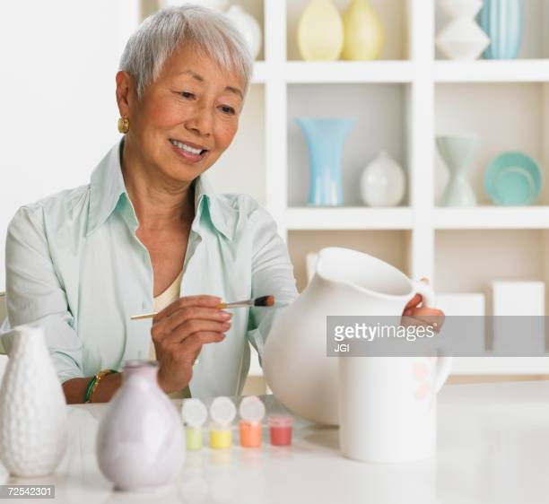 Senior Asian woman painting pottery