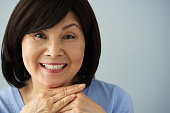Senior Asian woman resting chin on hands