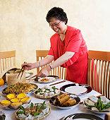 Senior Asian woman setting food on table