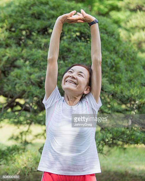 アジアの老人女性ストレッチと腕を頭の上に
