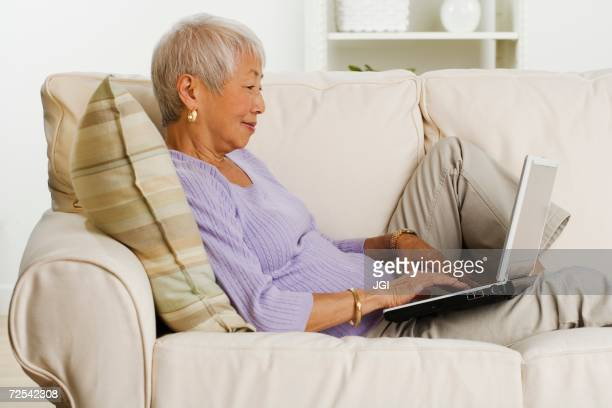 Senior Asian woman using laptop on sofa