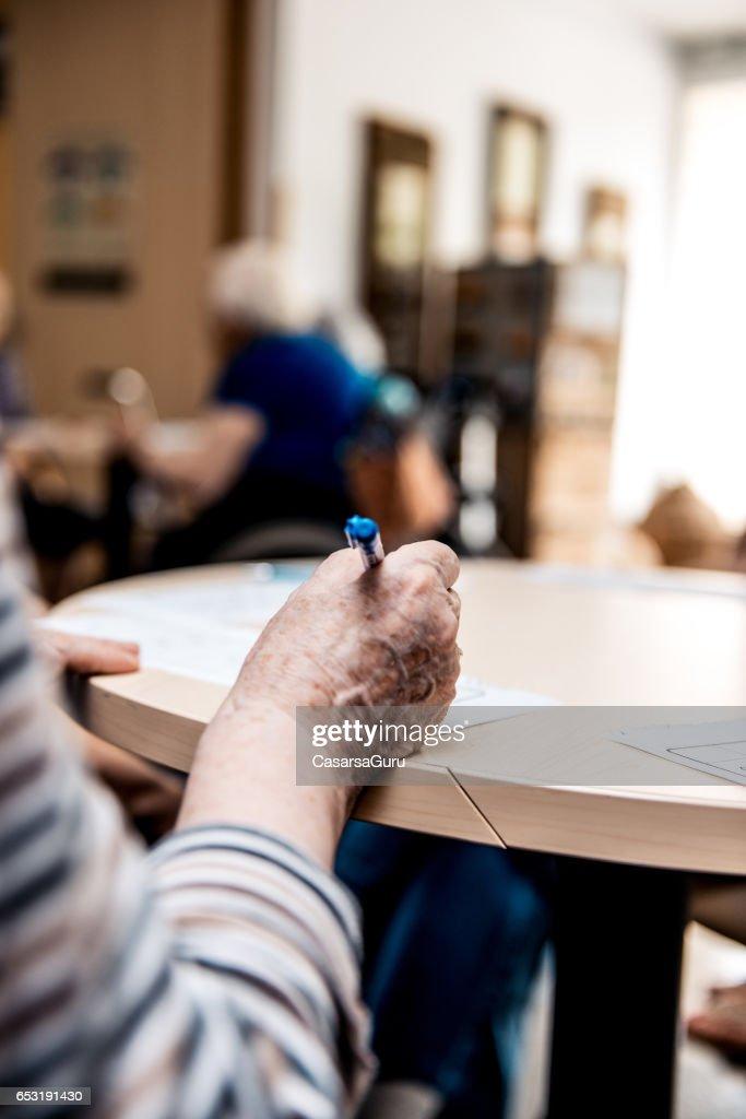 Senior in das Seniorenheim Kreuzworträtsel zu lösen : Stock-Foto