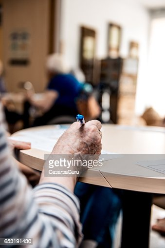 Senior At The Retirement Home Solving Crosswords : Stock-Foto