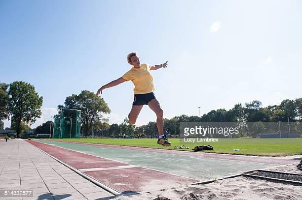 Senior athlete (75) practicing long jump