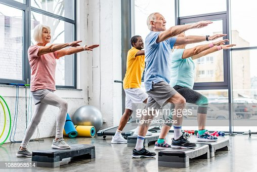 senior athletes synchronous exercising on step platforms at gym : Stock Photo