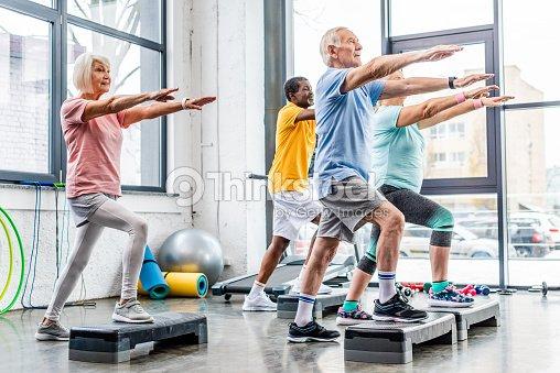 senior athletes synchronous exercising on step platforms at gym : Stock Photo