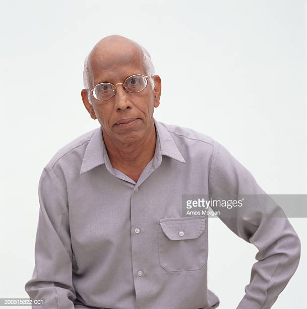 Senior balding man posing in studio frowning, portrait