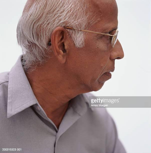 Senior balding man posing in studio looking away, close-up