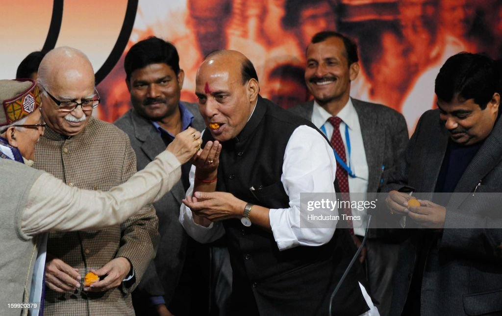 Senior BJP Leader Murli Manohar Joshi offer sweets to Newly elected BJP President Rajnath Singh while L K Advani and Former BJP President Nitin Gadkari looks on at BJP Headquarter, on January 23, 2012 in New Delhi, India. Rajnath Singh succeeds Nitin Gadkari, who decided against contesting for a second term following charges of alleged corruption.