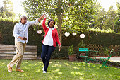 Senior black couple dance in their back garden, full length