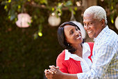 Senior black couple dancing in their backyard, close up