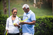 A senior black couple together on the tennis court.