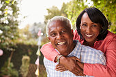 Senior black couple piggyback in garden looking at camera