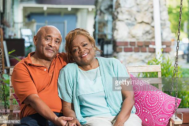 Senior black couple sitting on porch swing holding hands